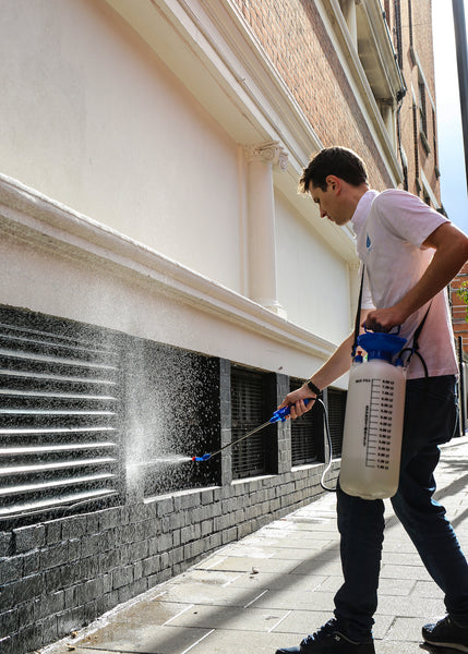 Liquiproof technician applies stone protector to wall