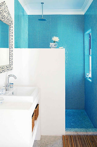 Turquoise tiles in shower with white cabinets
