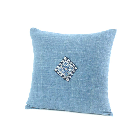 Square cotton pillow in light blue with embroidered detail.