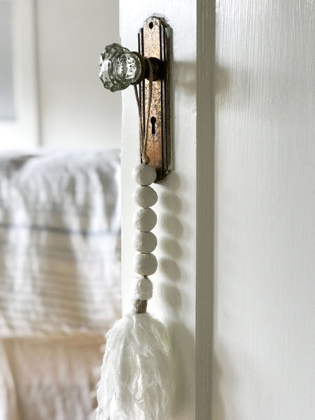 Harper & Wilde's muslin tassel hanging on doorknob