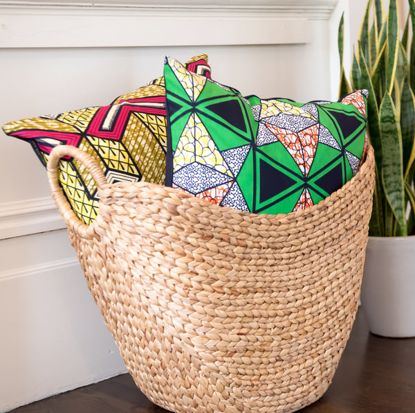 Colorful throw pillows of African-Dutch wax fabric in a basket.