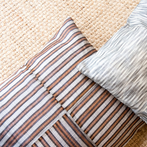 Large hinabol pillows in striped and ikat patterns.