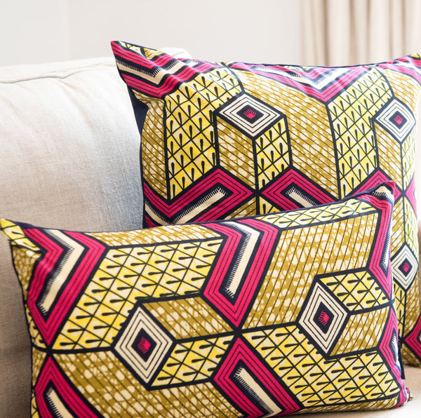 Fuscia and yellow African wax print pillows on sofa