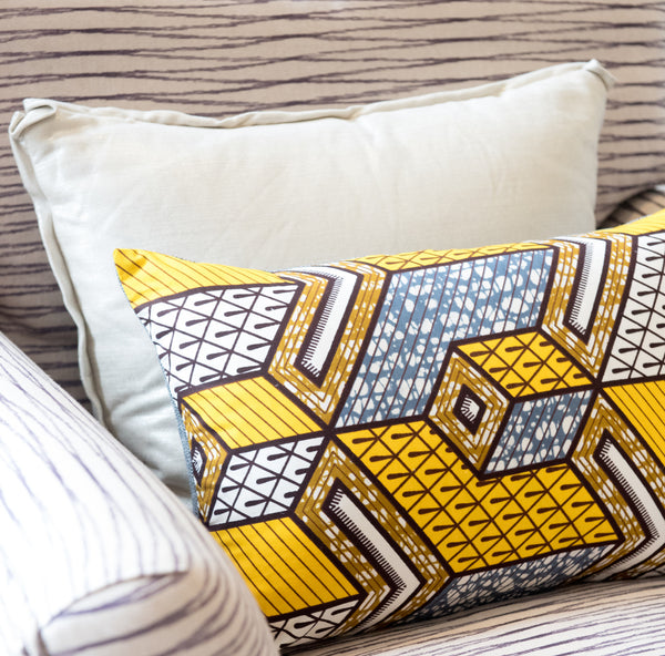 Yellow African wax print pillow on chair