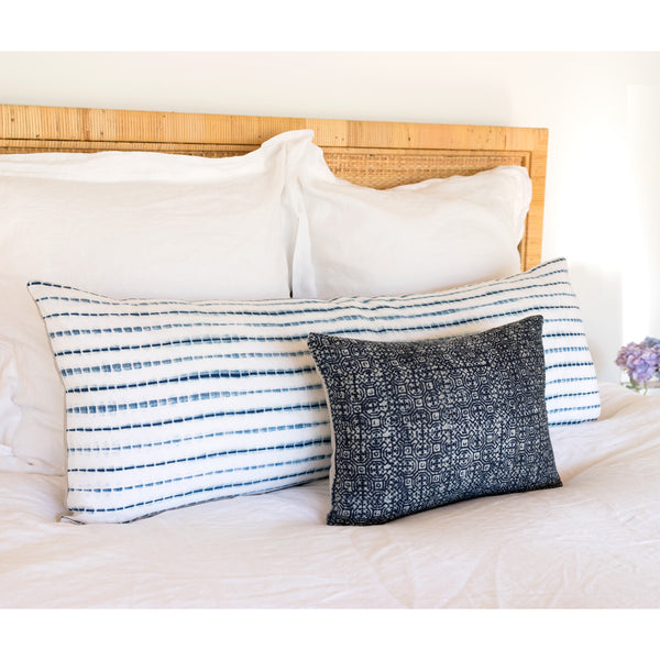 Indigo Batik Pillow I on bed with shibori