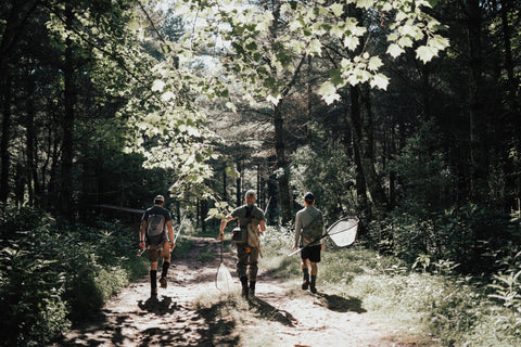 three men walking walking in the woods with their fly rods