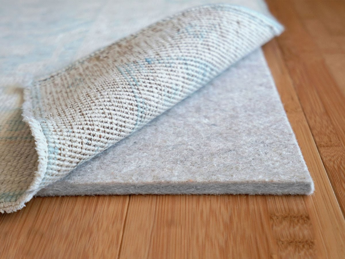 a cushioned rug pad acts as a barrier to protect a high traffic area rug