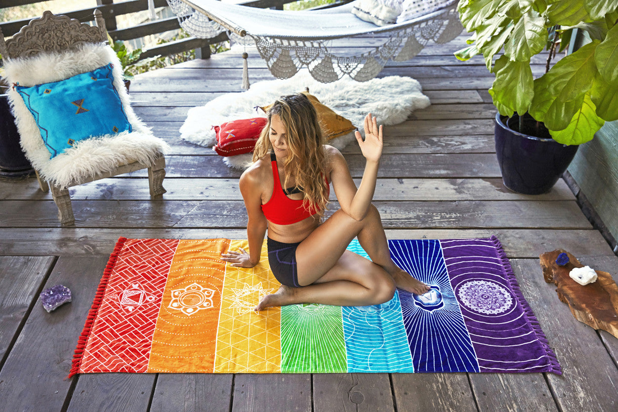 vagabond chakra towel on wood deck with a girl meditating - Beach Towel