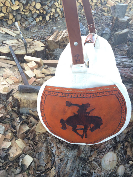 "Our Rodeo Gear Bag measures 24""x12"". This bag is built from our heavy 15 ounce canvas, has a #10  brass zipper, handles with a leather grip, leather shoulder strap and two leather end pockets that can be customized."