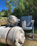 Two J bar D Cowboy Bedrolls laying in the grass next to a Yeti Chair and a Yeti Canteen. The background is a willow bush.