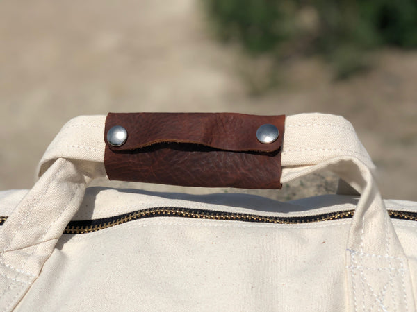 Our Rodeo Garrett bags are constructed from our heavy 15 ounce canvas, two end pockets, a stout brass zipper, leather gripper, with snaps, on the handles. A leather shoulder strap, which can be personalized