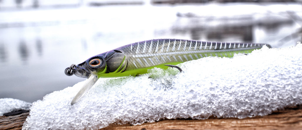 A medium diving jerkbait style bass crankbait that imitates a baitfish is sitting on snow in the winter