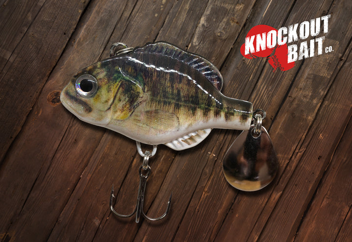 The Knockout Bait Company Suckerpunch is pictured with a bass paint job, a single treble hook and a single Indiana blade on the back.