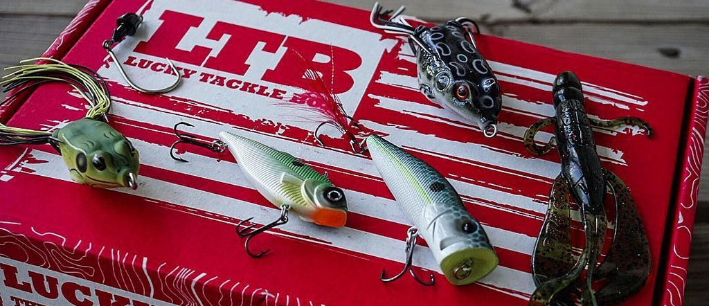 Multiple bass fishing lures and baits used to catch bass including topwater, plastics and hard baits sitting on top of a lucky tackle box subscription box.