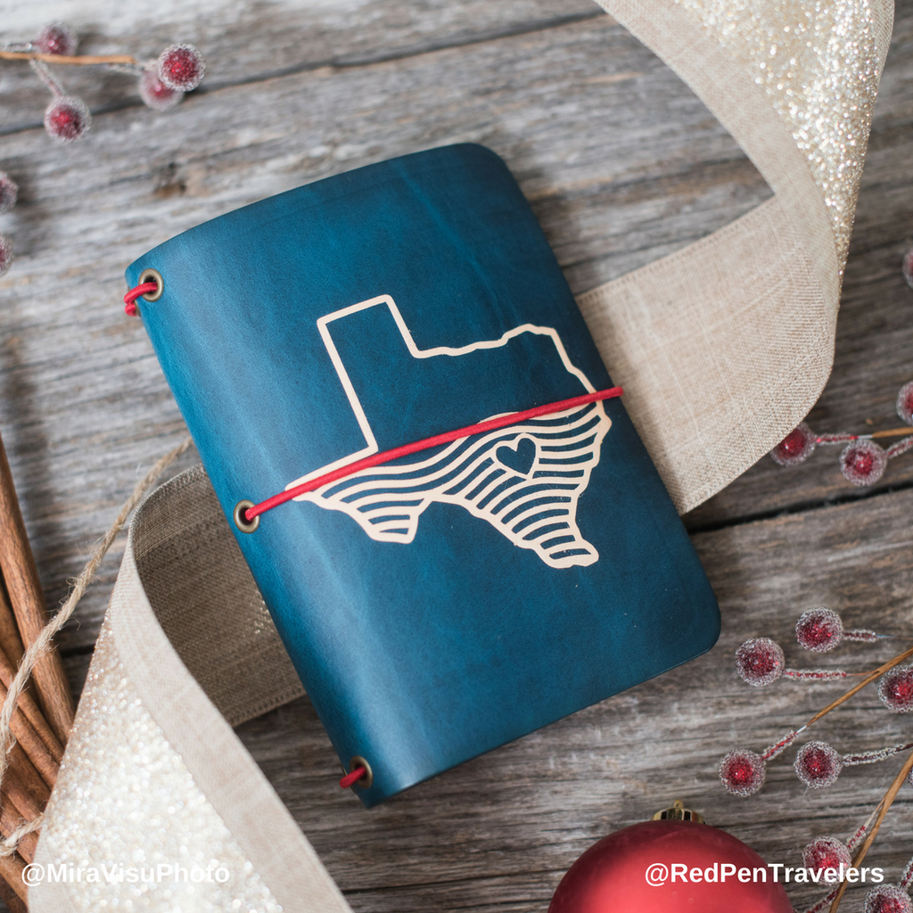 Midnight travelers notebook with the shape of Texas half-covered in water dyed into the cover, with cardinal elastic.