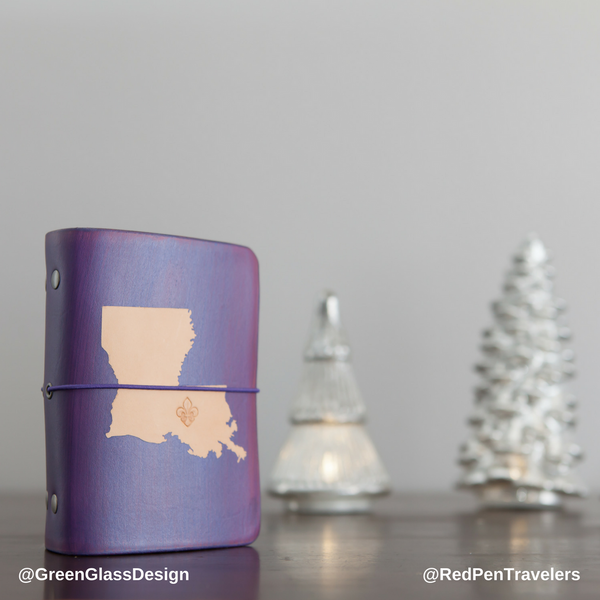 A purple travelers notebook with the shape of Louisiana dyed into the cover, next to white ceramic fir tree figurines.