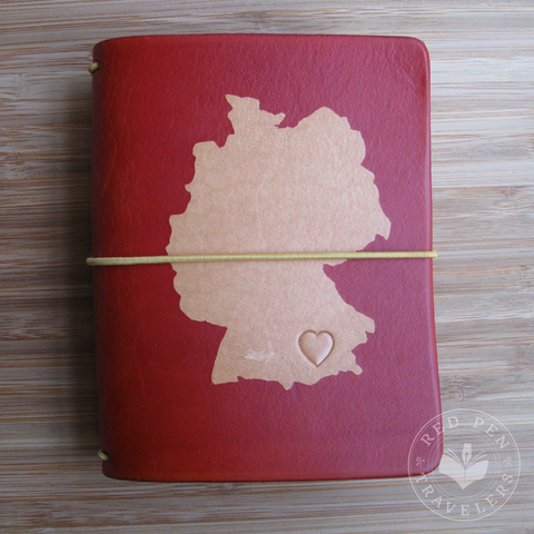 Cardinal travelers notebook with the shape of Germany dyed into the cover.