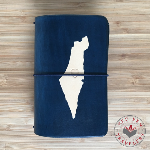 Midnight travelers notebook with the shape of Israel dyed into the cover and midnight elastic.