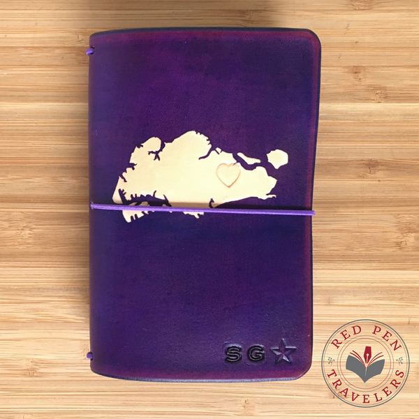 Purple travelers notebook with the shape of Singapore dyed into the cover.