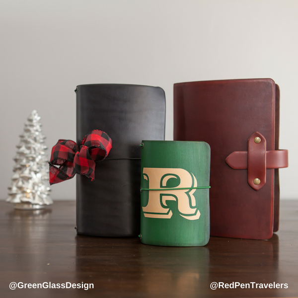 "Pine travelers notebook with a large ""R"" dyed into the color, in front of an espresso premium tab travelers notebook and a black travelers notebook with a Christmas bow, next to a white ceramic fir tree."