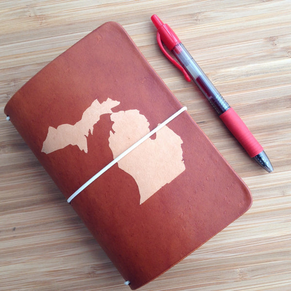 Espresso travelers notebook with the shape of Michigan dyed into the cover.