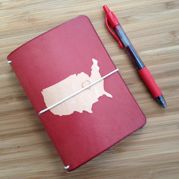 Cardinal travelers notebook with the shape of the contiguous United States dyed into the cover, shown lying next to a red pen.