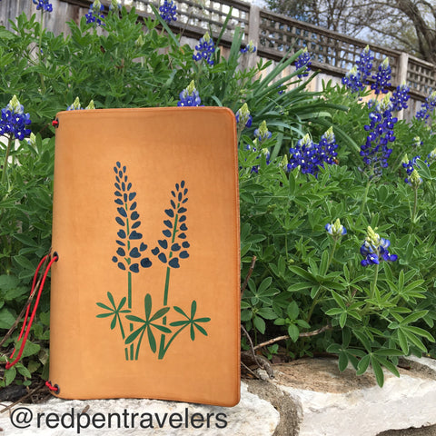 Undyed travelers notebook with bluebonnet design on front, shown with a background of live bluebonnets.
