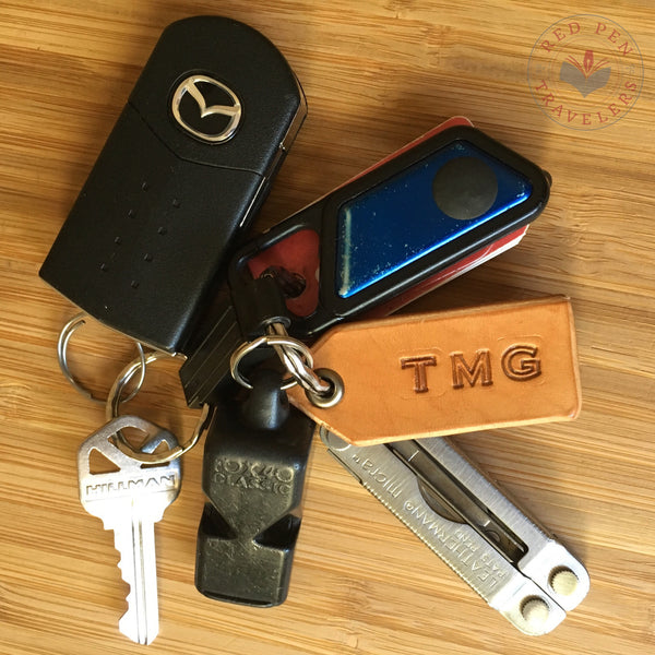 "Leather tag engraved ""TMG"" on keyring full of keys and mini-tools."