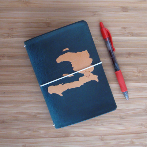 Midnight travelers notebook with the shape of Haiti dyed into the cover with turquoise elastic and a red pen.