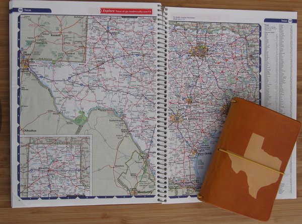 Marigold travelers notebook with the shape of Texas dyed into the cover, shown lying on a map.