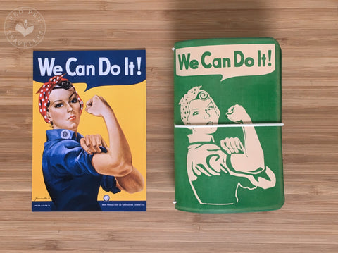 """We Can Do It"" Rosie the Riveter poster next to a pine and undyed travelers notebook featuring the same words and design with turquoise elastic."