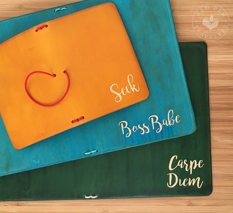 "Travelers notebooks with ""Seek"", ""Boss Babe"", and ""Carpe Diem"" dyed into the covers."