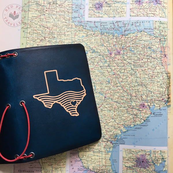 "Midnight ""Hell or High Water"" travelers notebook with cardinal elastic, turned over flat on a map of Texas."