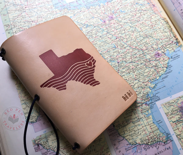 "Undyed travelers notebook with mahogany ""Hell or High Water"" design dyed into the cover, on a map of Texas."