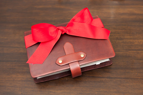 Mahogany tab closure travelers notebook decorated with a large, bright red bow.