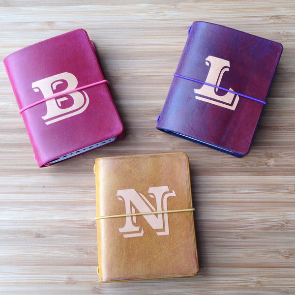 "Hot pink, purple, and tan travelers notebooks, with large letters ""B"", ""L"", and ""N"" dyed into their covers."
