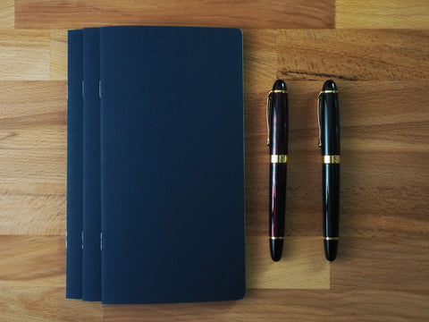 Three navy travelers notebook inserts with two black pens.
