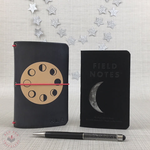 Midnight travelers notebook with eight phases of the moon dyed into a circle on the cover; Field Notes insert with a crescent moon on the cover; black pen; silver stars hanging in background.