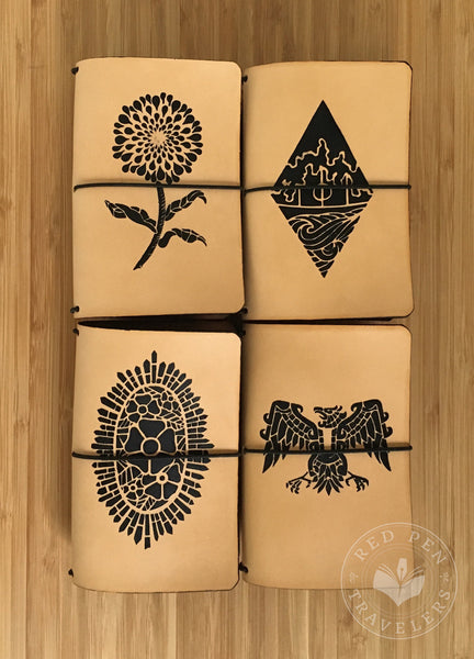 Undyed travelers notebooks in four black-only designs: Black Zinnia, Hidden Village, Cathedral Rose, and Aztec Eagle.