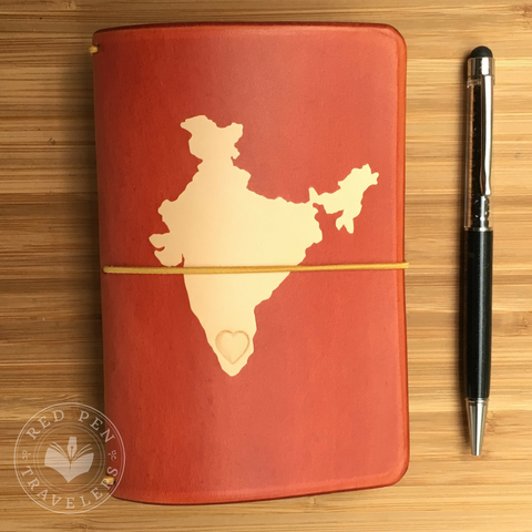 Butterscotch travelers notebook with the shape of India dyed into the cover, with yellow elastic and black pen.