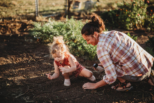 Mom and daughter planting raised bed