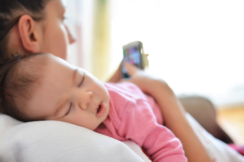 mom using a baby tracker app while breastfeeding her baby