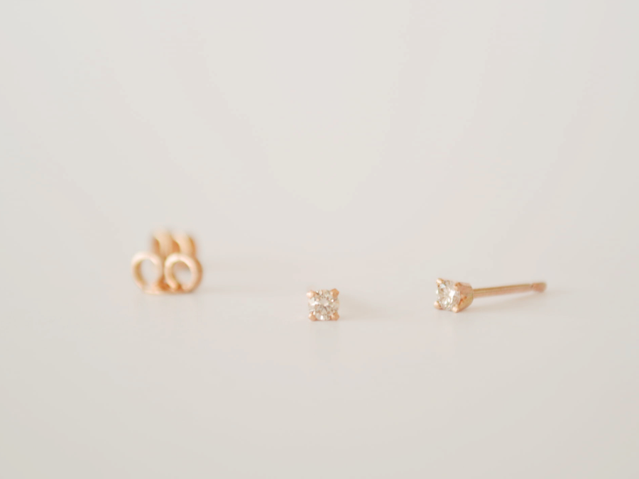 A pair of 9ct Yellow Gold Stud Earrings with 2.4mm Diamonds on a Grey Background