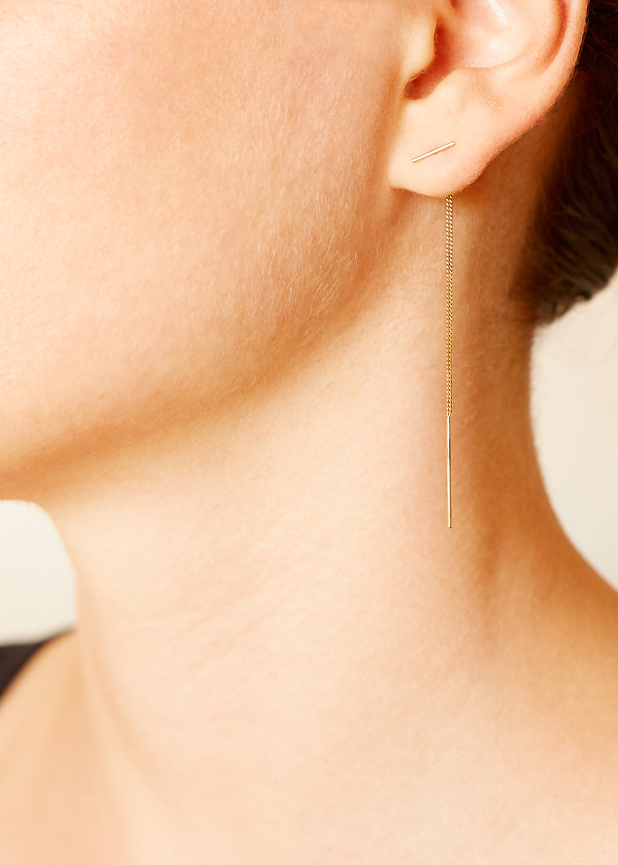 A model wearing a 9ct yellow gold thread earring with a small bar