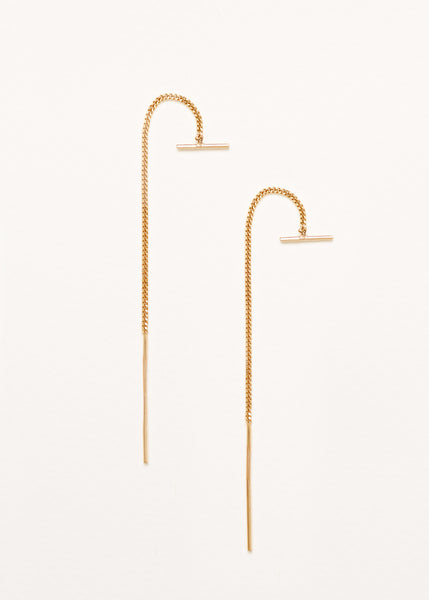 A pair of 9ct yellow gold thread earrings with a small bar on a grey background