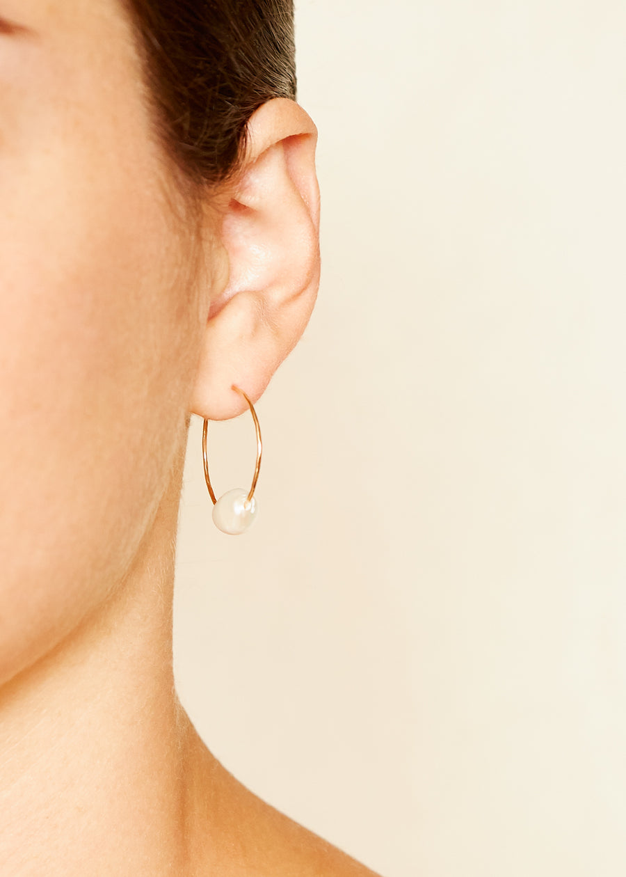 A model wears a Gold Filled 925 Sterling Silver Hoop Earring with a single Freshwater Pearl