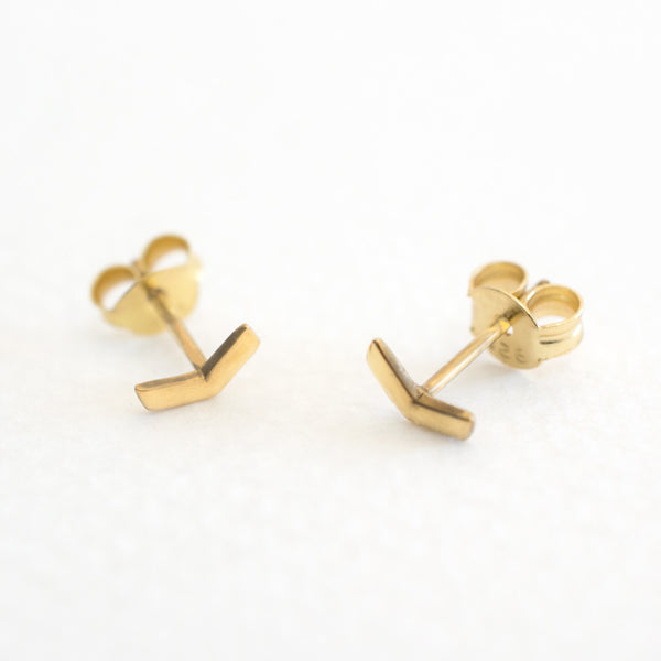 A pair of 18ct gold plated 925 sterling silver chevron arrow stud earrings on a grey background