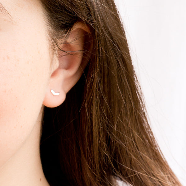 A young female model wears a pair of 18ct gold plated 925 sterling silver chevron arrow shaped stud earrings.