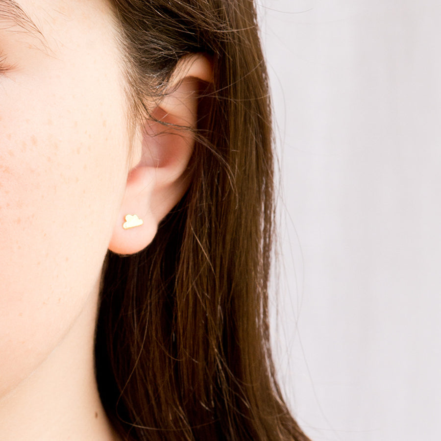 A young brunette model wears a 925 sterling silver cloud shaped stud earring, with a grey background to the right
