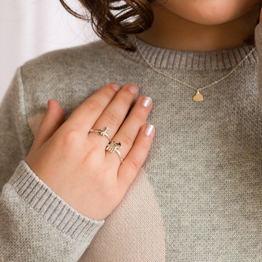 A young model wears small sterling silver rings against their grey knit sweater